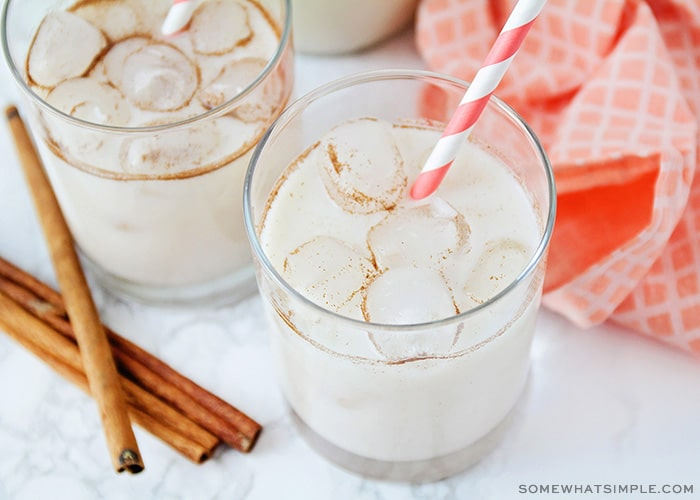looking down on two glass filled with horchata and ice. Each cup has a striped straw inside and there are cinnamon sticks laying on the counter next to the glasses.