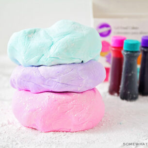 three flattened balls of marshmallow fondant stacked on top of each other on a counter covered with powdered sugar. The ball of fondant on top is light blue, the middle one is light purple and the bottom one is light pink. In the background are three bottles of Wilton gel food coloring.