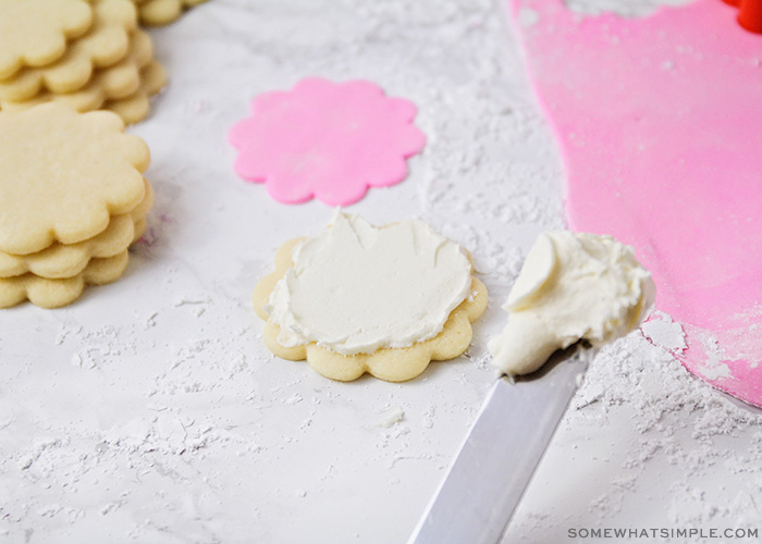 a sugar cookie with white fondant made from marshmallows is on a counter. Hoovering over the air is an icing spatula with a glob of fondant on the tip. Next to the cookie are stacks of additional unfrosted flower-shaped sugar cookies. On the other side of the image is flattened pink marshmallow fondant.