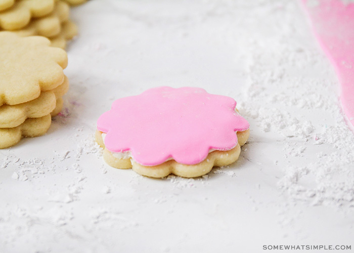 a sugar cookie in the shape of a flower is topped with pink homemade marshmallow fondant.