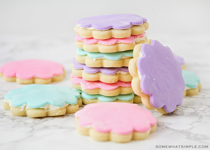 a stack of sugar cookies topped with either pink, light green or purple marshmallow fondant. One cookie with purple fondant is on it's side leaning against the stack of cookies and a few other cookies are laying flat on the counter around the stack.