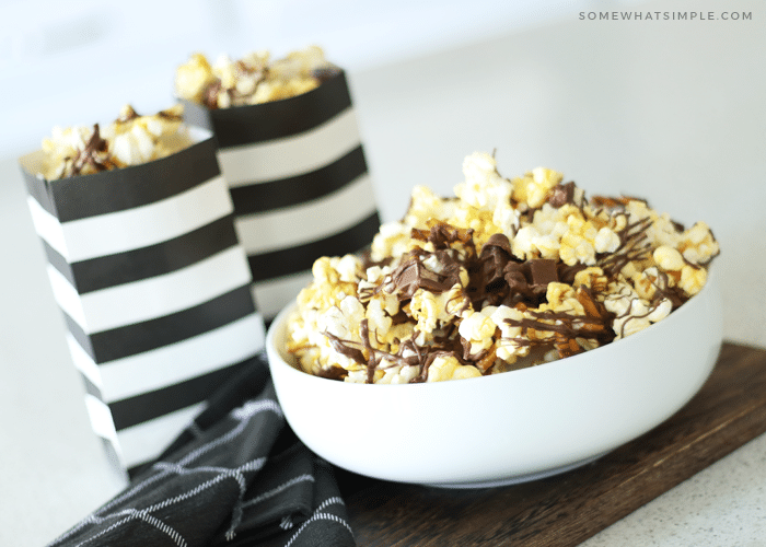 a white bowl filled with gourmet popcorn with drizzled chocolate on top mixed with pieces of kit kat bars and pretzels. Behind the bowl are two black and white striped bags filled with more chocolate covered popcorn
