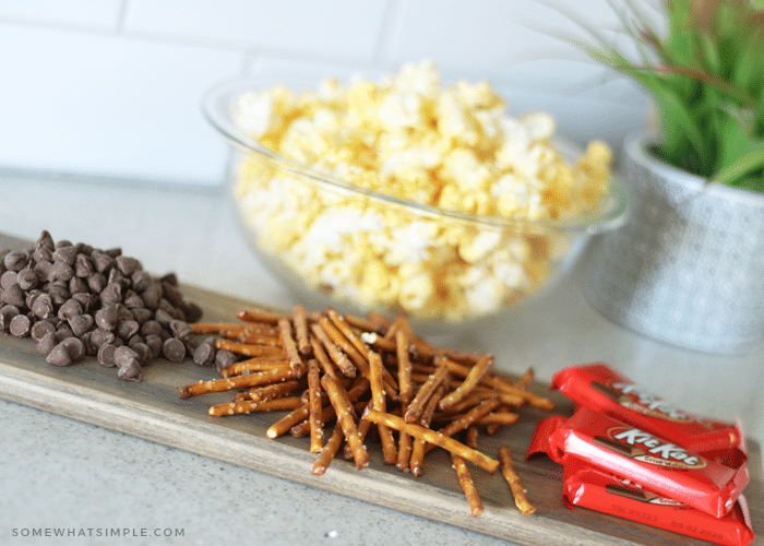 a bowl of popped popcorn sitting on the counter behind piles of chocolate chips, pretzel sticks and kit kat bars which are the ingredients for this gourmet chocolate popcorn