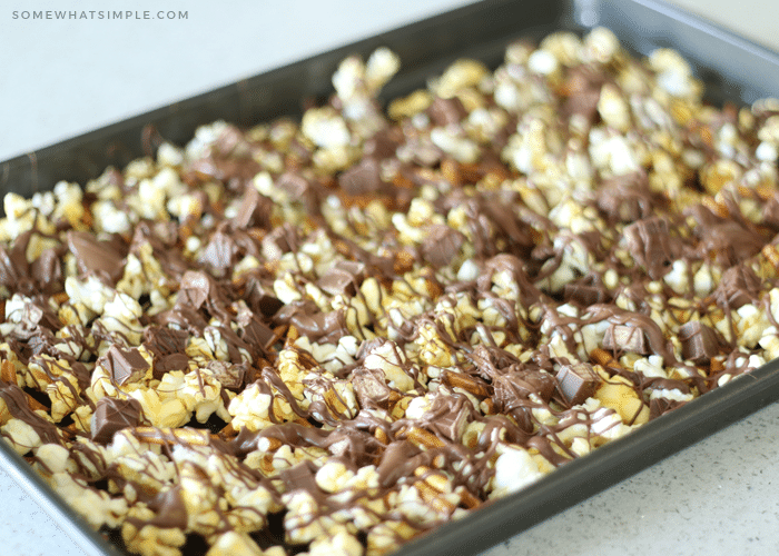 a baking sheet of gourmet popcorn mixed with small pieces of kit kat bars and pretzels with drizzled chocolate over the top