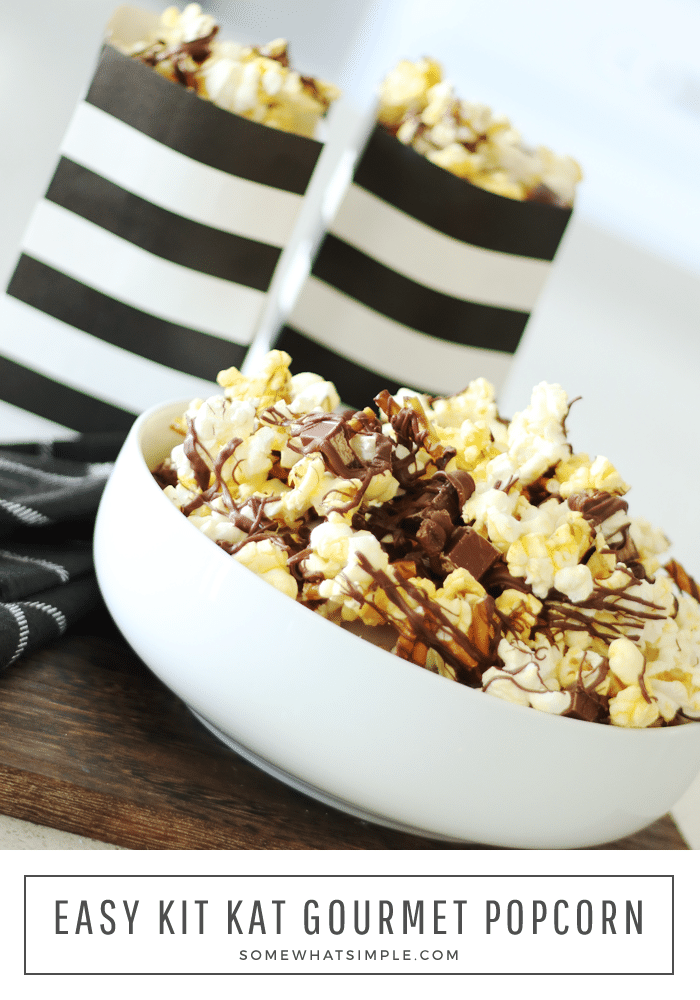 a white bowl filled with gourmet popcorn with drizzled chocolate on top mixed with pieces of kit kat bars and pretzels. Behind the bowl are two black and white striped bags filled with more chocolate covered popcorn with the words easy kit kat gourmet popcorn written at the bottom of the image