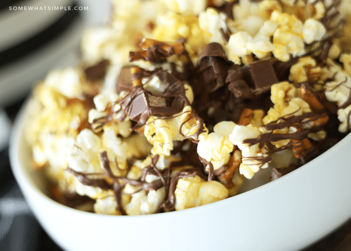 a close up of a white bowl of gourmet popcorn mixed with small pieces of kit kat bars and pretzels with drizzled chocolate over the top that was made using this easy recipe