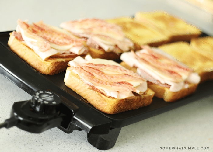 slices of bread cooking on top of a black griddle. The bread on the left side of the griddle are topped with ham, turkey and bacon, while the slices on the right side don't have anything on top of them.