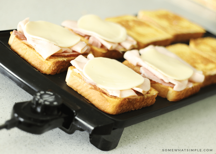 slices of bread cooking on top of a black griddle. The bread on the left side of the griddle are topped with ham, turkey and white cheese, while the slices on the right side are golden brown but don't have anything on top of them.