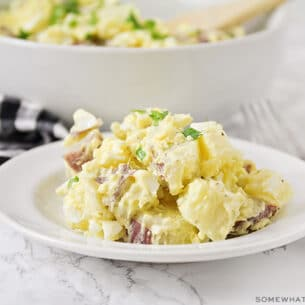 a plate with a serving of potato salad made with mustard and hard boiled eggs.