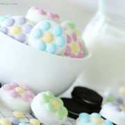 a white bowl filled with chocolate covered Oreos that have pastel colored m&ms on them. On the counter next to the bowl are more chocolate covered oreos and regular oreos with a pitcher of milk in the background.