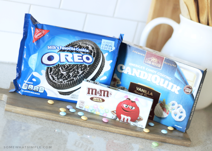 a package of oreos, a box of m&ms and a box of baking chocolate on a counter which are the ingredients to make chocolate covered oreos.