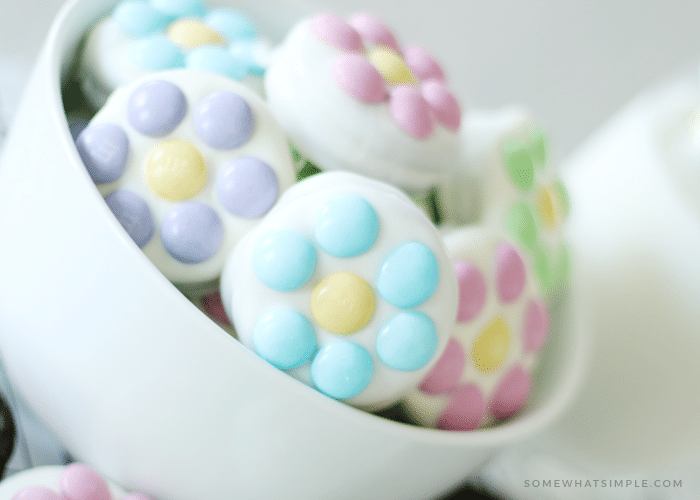 a close up picture of a white bowl filled with white chocolate covered Oreos with pastel colored m&ms
