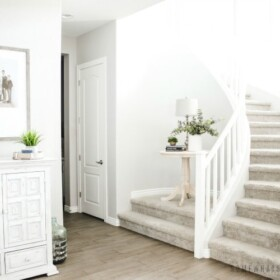 the entry way of a home with a winding staircase. A small wooden table is on an elevated landing. There is also a large white cabinet along the wall in the entry way.