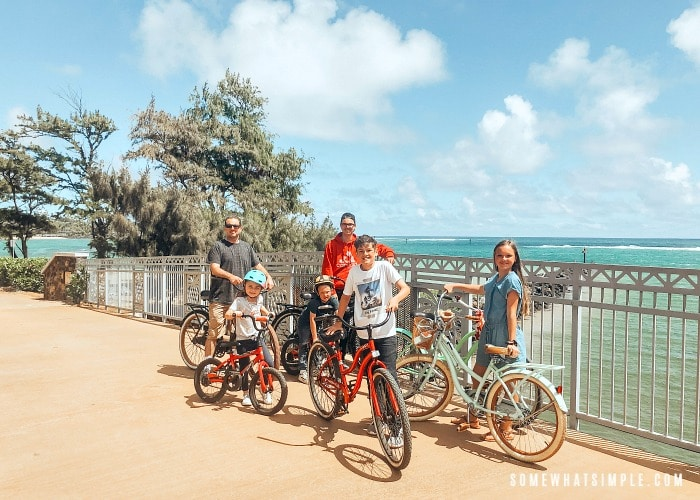 a dad with five of his kids standing next to bikes on a bridge with a beach in Kauai in the background