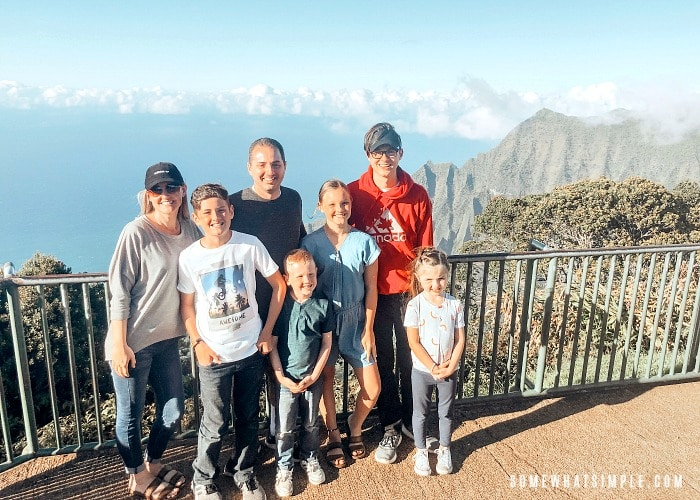 a good looking family of seven standing by a fence overlooking the Kalalau Valley and the ocean