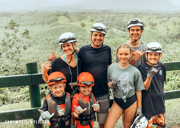 an attractive mom and dad with their five kids most wearing helmets with head lamps, who are getting ready for a tubing adventure, overlooking lush green hills in kauai