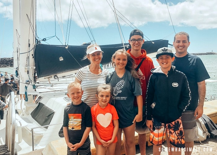 a good looking mom, her husband and five kids standing in front of a catamaran before sailing with Captain Andy's