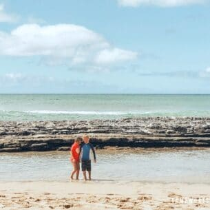 two children playing at Salt Pond beach in Kauai Hawaii