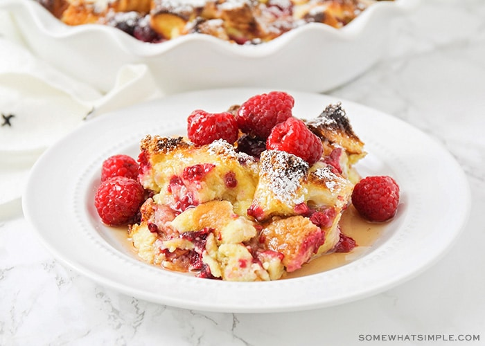 a white plate filled with baked raspberry french toast that is topped with fresh whole raspberries and syrup
