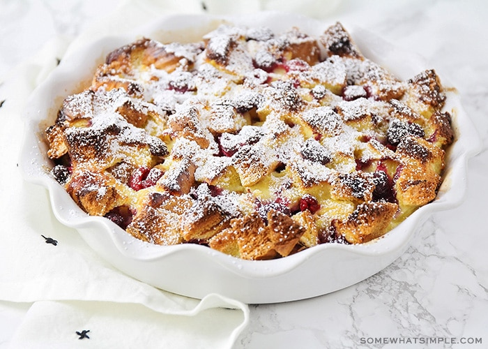 a baking dish with filled with this easy baked raspberry french toast recipe topped with powdered sugar