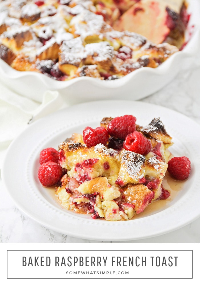 a white plate with a serving of raspberry french toast that is topped with fresh whole raspberries and syrup. At the bottom of the image, the words baked raspberry french toast are written within a white box