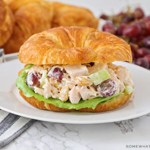 a chicken salad sandwich made with a croissant on a white plate. More croissants and a pile of grapes are laying on the counter behind the plate