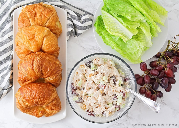 a bowl of chicken salad next to a tray of croissants, grapes and leaves of lettuce
