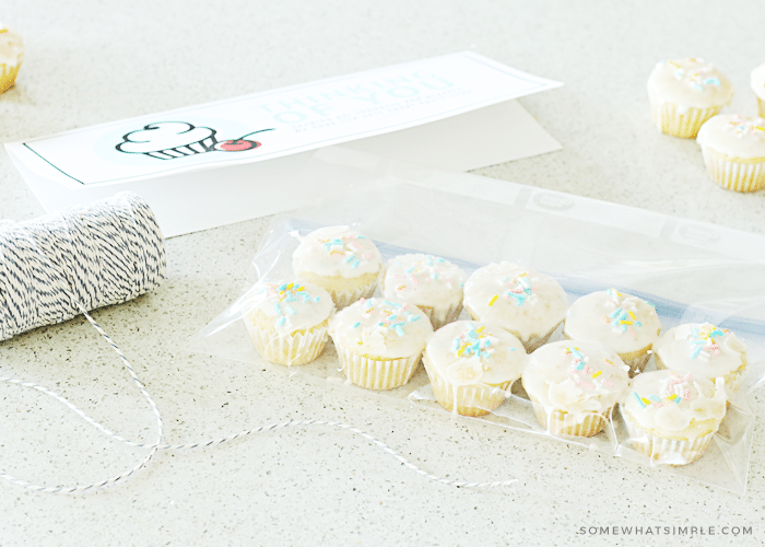 a gift tag printable, baker's twine and a bag with mini cupcakes inside sitting on a counter