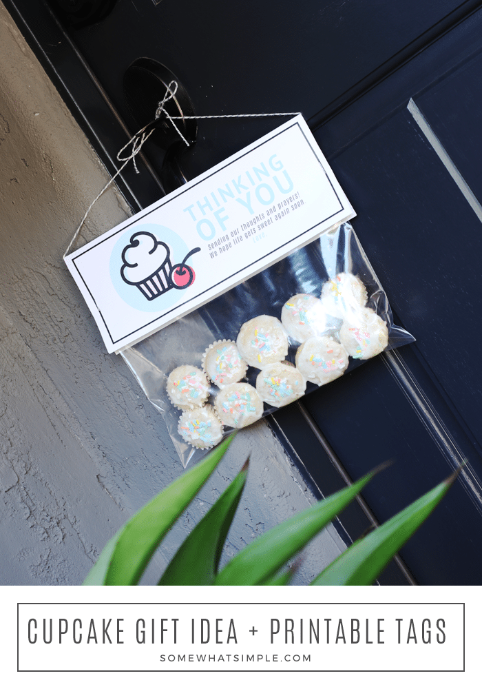 a cupcake gift hanging from a black door. at the bottom of the image the words cupcake gift idea + printable tags is written in a white box