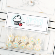 a bag filled with ten mini cupcakes topped with sprinkles with a gift tag attached that says thinking of your with a picture of a cupcake and a cherry on it