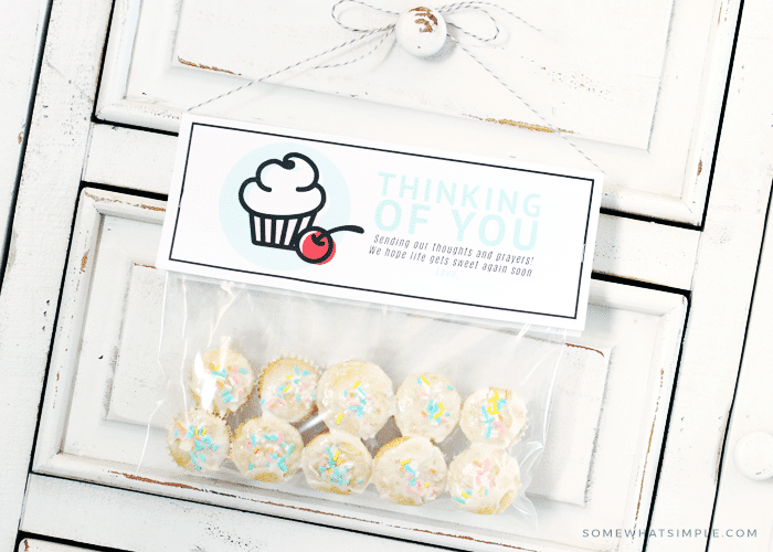 a bag of mini cupcakes with a gift tag attached hanging from a door