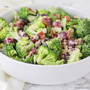 a white bowl filled broccoli salad with sliced grapes and pieces of bacon