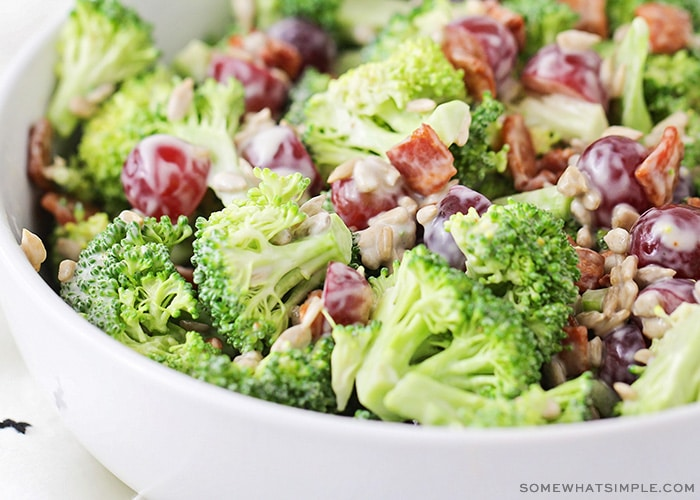a close up of a bowl filled with pieces of broccoli, bacon, grapes topped with a dressing