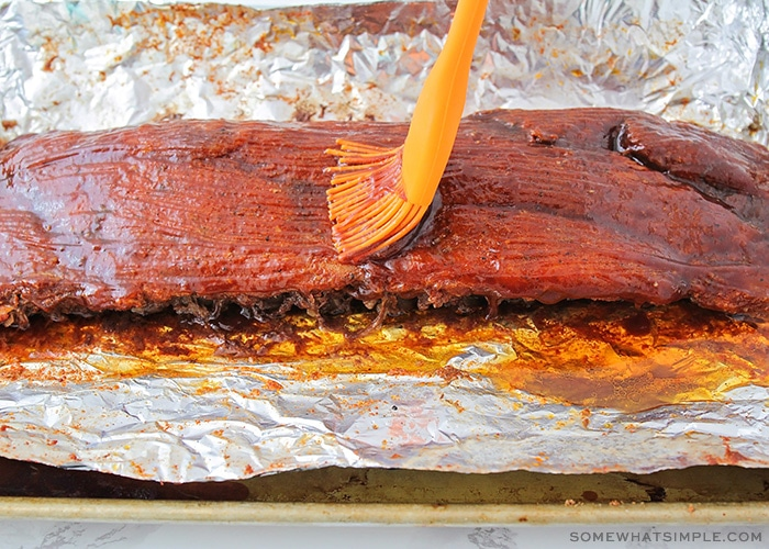 an orange basting brush spreading bbq sauce over a cooked rack of ribs