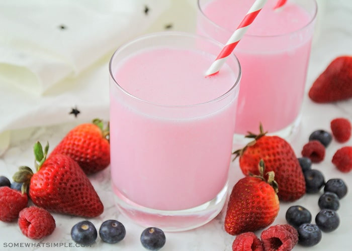 a glass filled with a pink yogurt drink with a striped straw in the cup. Surrounding the glass are several strawberries, blueberries and raspberries.