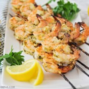 several skewers of grilled pesto shrimp fresh off the BBQ and laying on a white serving platter.