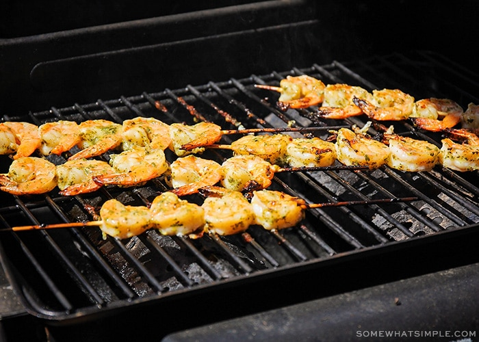shrimp on wooden skewers being cooked on a barbecue