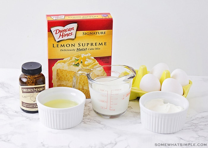 a box of lemon supreme duncan hines cake mix, a jar of vanilla, butter, milk, eggs and sugar sitting on a counter
