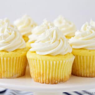 a white cake stand with several lemon cupcakes topped with a cream cheese frosting and white sprinkles. There are a couple of lemons on the counter next to the cake stand.