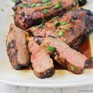 slices of steak that have been soaked in this quick steak marinade recipe on a white platter with juices pooling at the bottom of the platter.