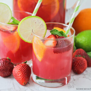 two glasses of non-alcoholic sangria punch that has a light pink color. slices of strawberries and oranges are floating in the cup with a slice of lime sitting on the rim of the glass. Fruit is scattered on the counter around the glass with a pitcher full of punch behind them.