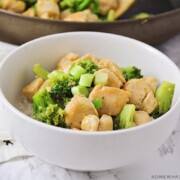 a white bowl filled with broccoli and chicken stir fry topped with chopped green onions all over a bed of white rice