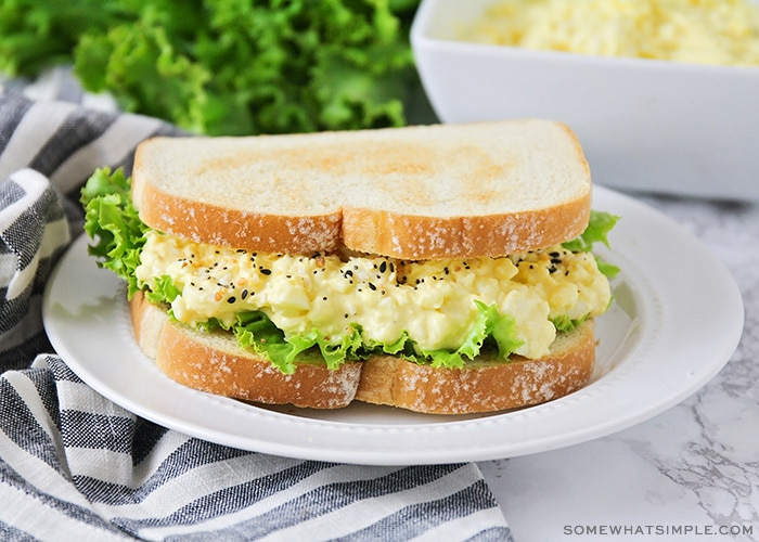 an egg salad sandwich on a white plate topped with lettuce on toasted white bread