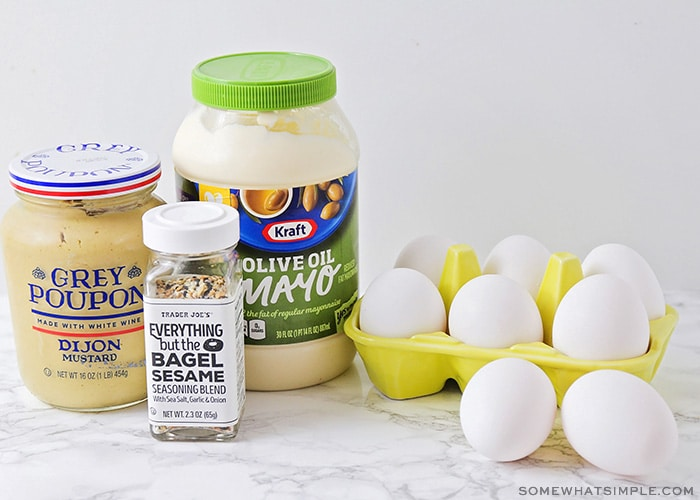 A bottle of Dijon mustard, mayo, eggs and a jar of seasoning on a counter
