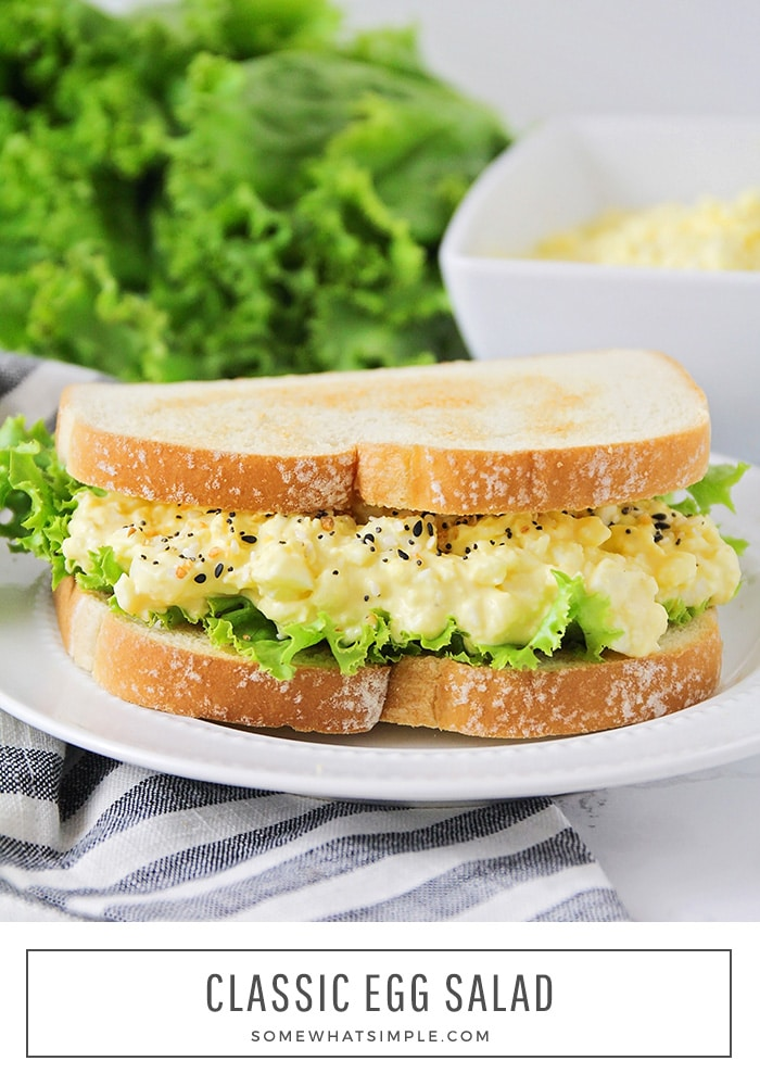 a close up of a sandwich made with this classic egg salad recipe with pepper sprinkled on top. a bowl of more egg salad and a pile of lettuce is in the background.