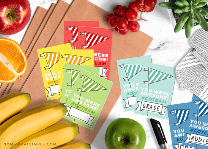 different colored team snack bag printables spread out on the counter