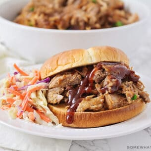 a pulled pork sandwich made in a slow cooker topped with bbq sauce and a side of coleslaw on a white plate.