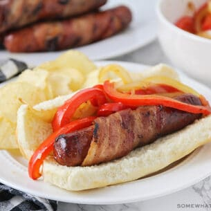 a hot dog wrapped in bacon on a bun, topped with grilled onions and red bell peppers with a side of potato chips on a plate.