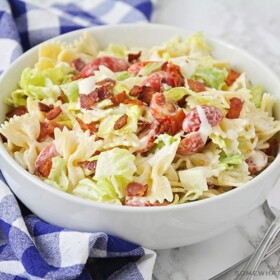 a white bowl of bow tie BLT pasta salad with lettuce, bacon and tomatoes.