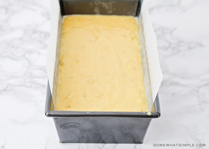 cake mix banana bread batter in a bread pan that is lined with parchment paper